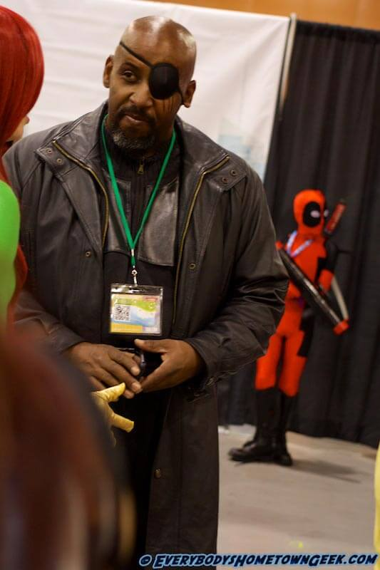 Nick Fury taking care of business at Phoenix ComiCon 2015 while  a young Deadpool lurks in the background.