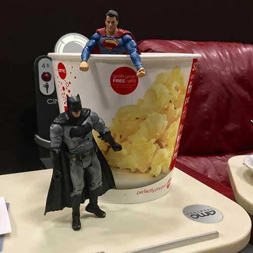 Batman and Superman at the movies together sharing popcorn. No need to fight, boys!